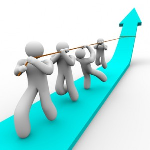 A team works together to pull up a growth arrow